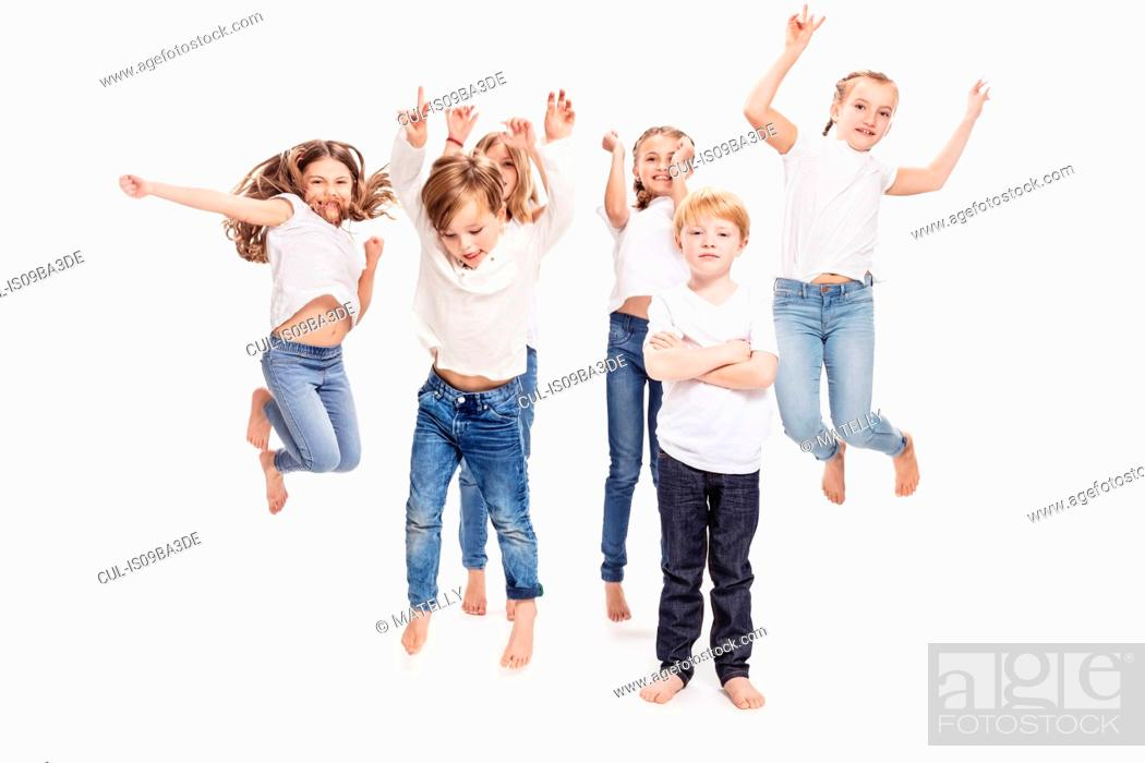 Stock Photo: Studio portrait of two boys and four girls having fun jumping mid air, full length.