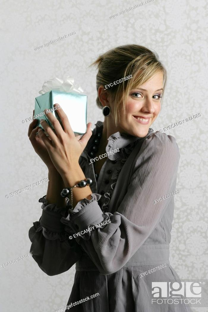 Stock Photo: Young woman holding gift box.