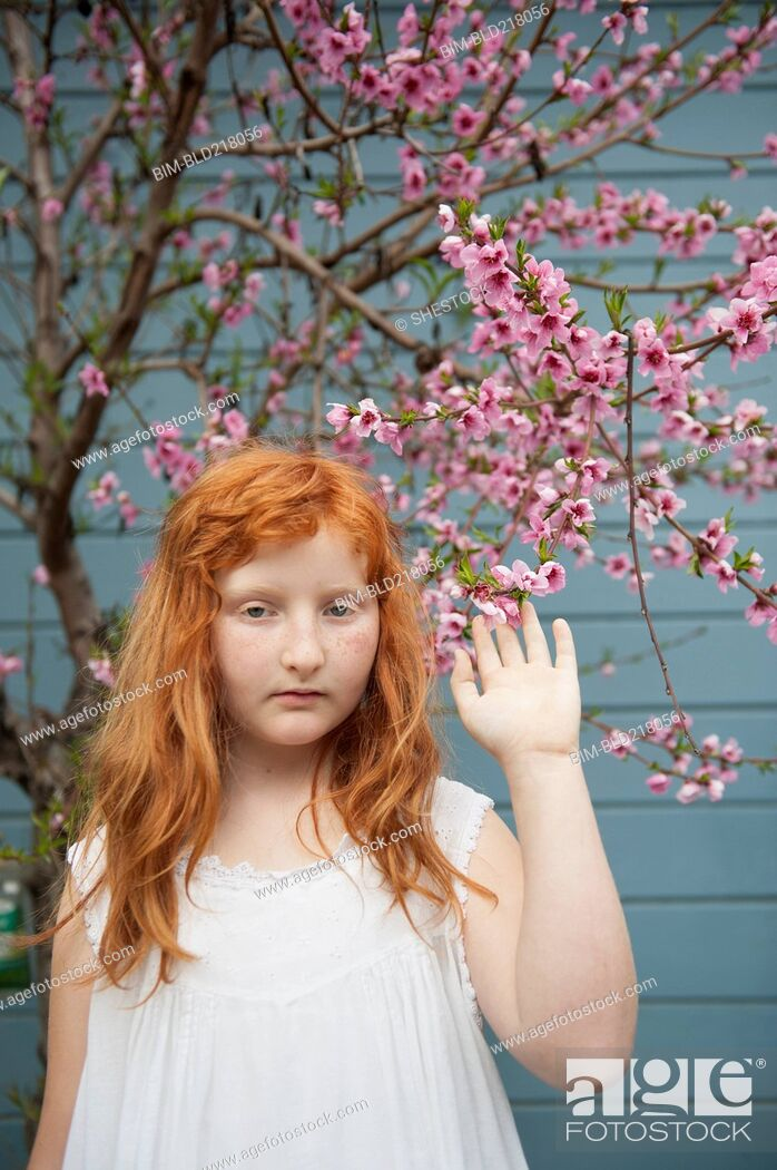 Stock Photo: Caucasian girl waving under flowering tree.