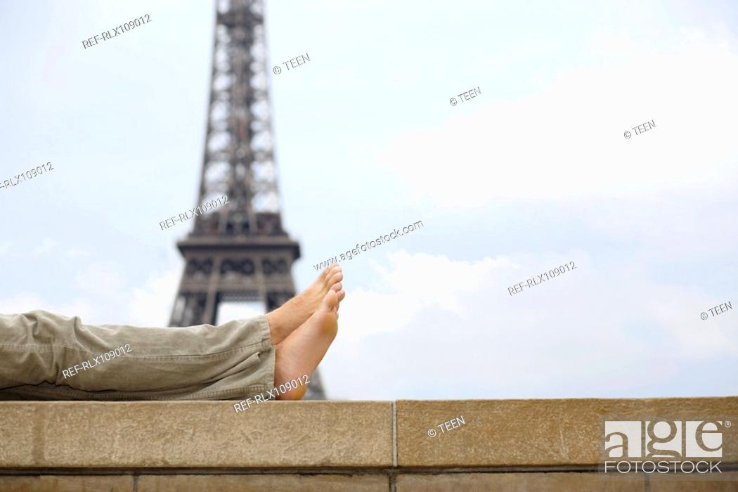 Stock Photo: Close up of mans legs with Eiffel tower in background, Paris, France.