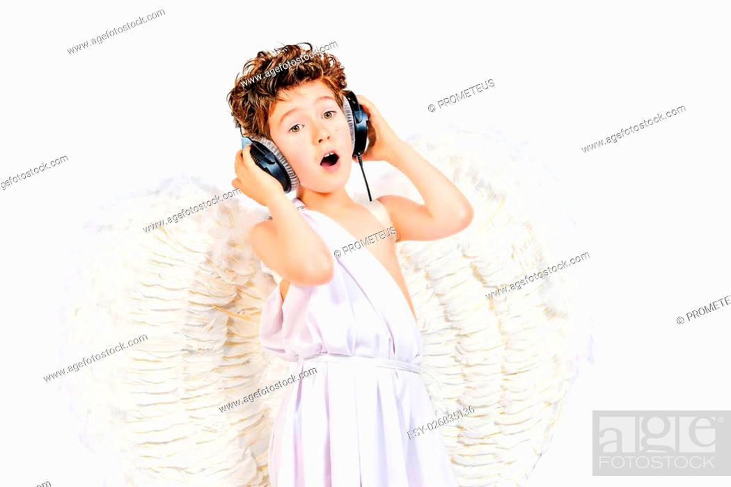 Stock Photo: Happy little boy in a costume of angel listening to music in headphones. Cupid. Valentine's day.