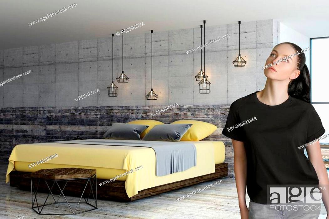 Stock Photo: thinking woman in loft bedroom with concrete wall above wooden bed.
