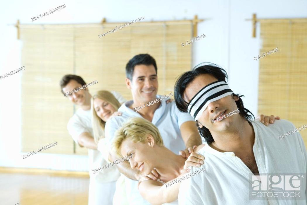Stock Photo: Group therapy, standing in single file line with hands on each other's shoulders.