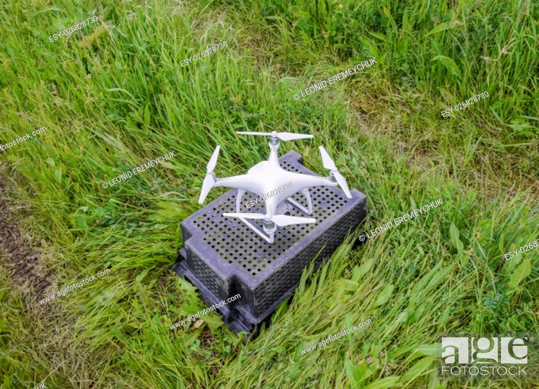 Stock Photo: Quadrocopters on a plastic box in the grass. Preparation quadrocopter to fly.
