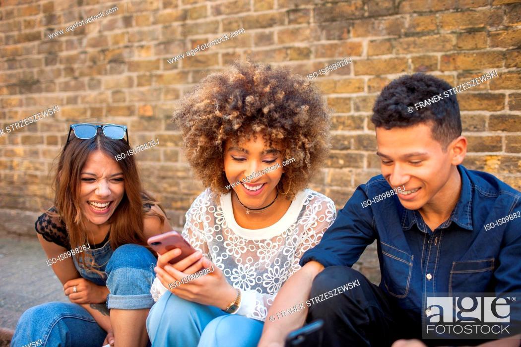 Imagen: Three friends sitting in street, looking at smartphone.