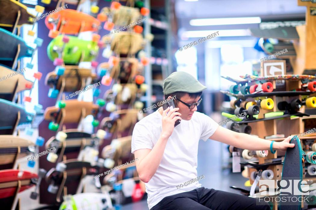 Stock Photo: Young male skateboarder making smartphone call in skateboard shop.