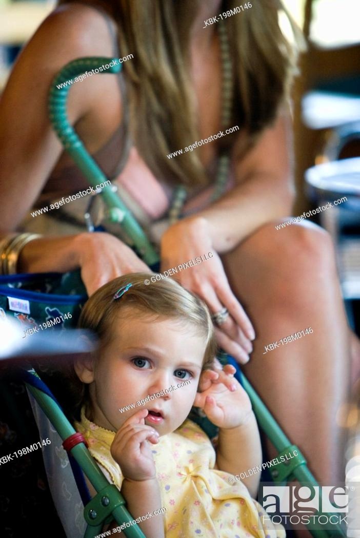 Stock Photo: Baby girl sitting in stroller in cafi with mom in background.
