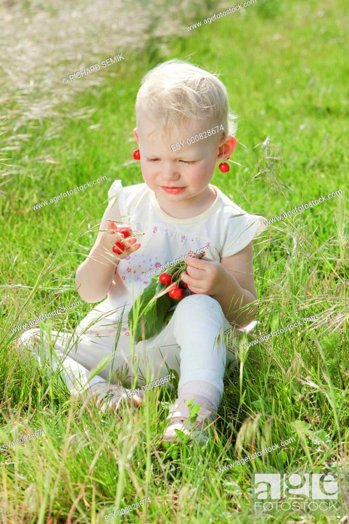 Stock Photo: little girl with cherries sitting on grass.