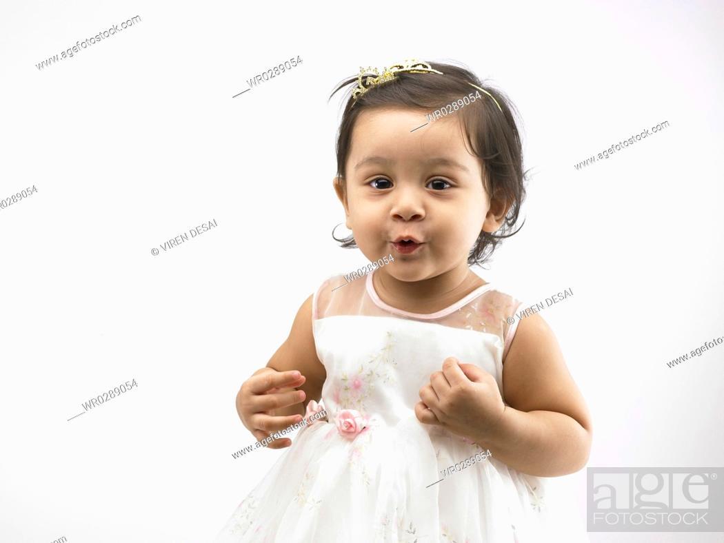 joyful indian baby girl wearing white dress making funny face mr702o