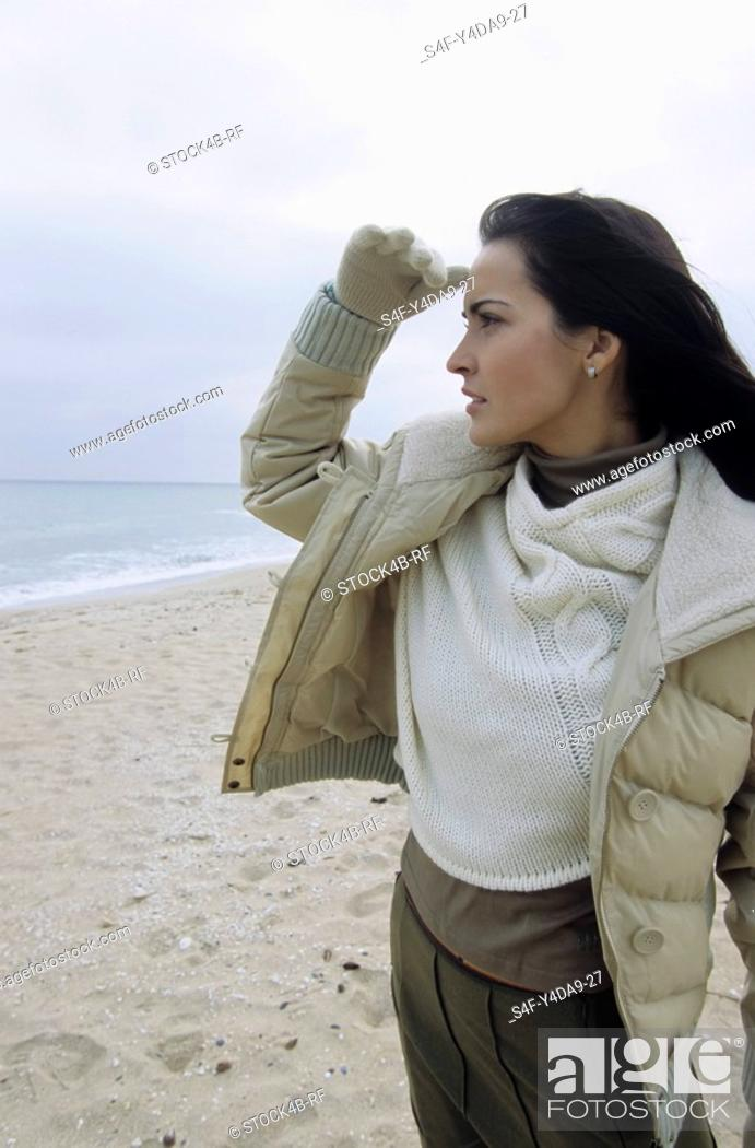 Stock Photo: Young brownhaired Woman watching out for something - Winterly Clothing - Season - Beach.