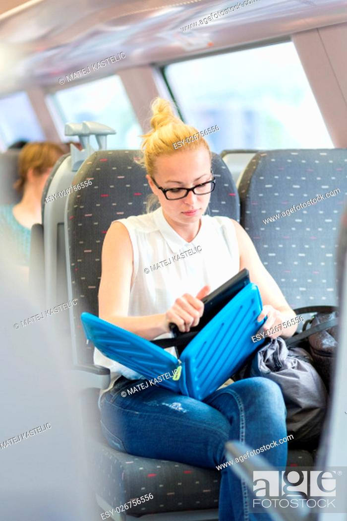 Stock Photo: Businesswoman sitting and traveling by train working on laptop. Business travel concept.