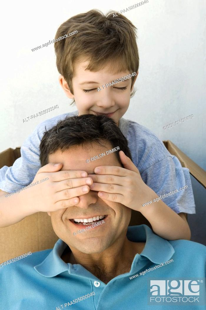 Stock Photo: Boy with hands over his father's eyes, both smiling, boy's eyes closed.