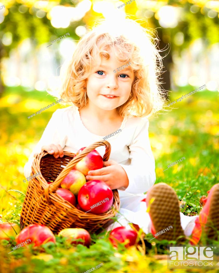 Stock Photo: Child with basket of apples.