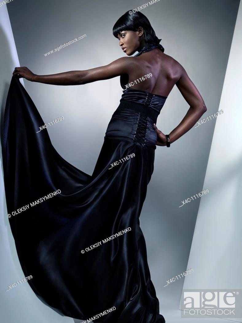 Stock Photo: Beautiful young woman wearing long black dress standing with her back to the camera  High fashion photo.