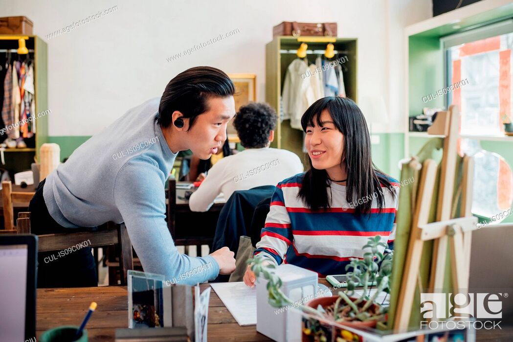 Stock Photo: Young businesswoman and man talking at cafe table.