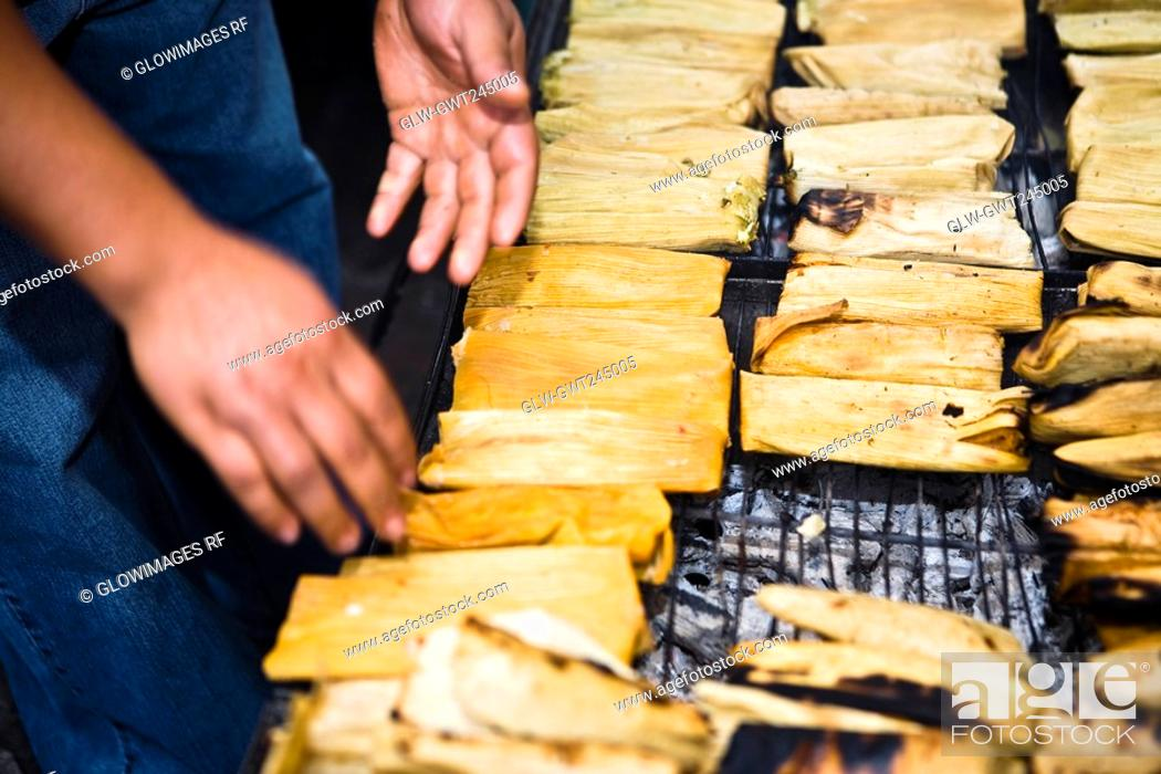 Stock Photo: Mid section view of a man roasting tamales on barbecue grill, Zacatecas State, Mexico.