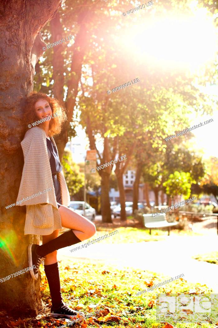 Stock Photo: Woman leaning on tree in park.