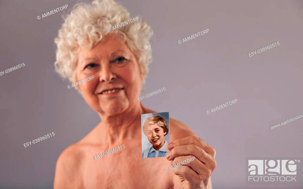 Stock Photo: Portrait of a senior women holding her old photo. Beautiful woman shirtless showing a vintage photograph of her young age. Memory of her young days.