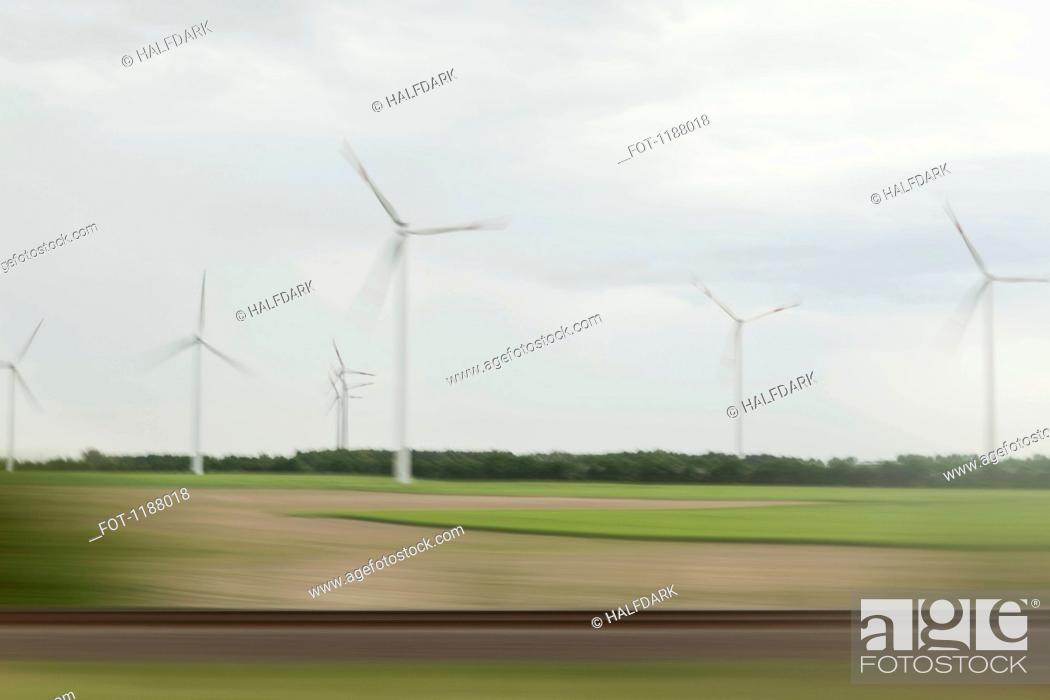 Stock Photo: Wind turbines and landscape in blurred motion viewed from moving train.