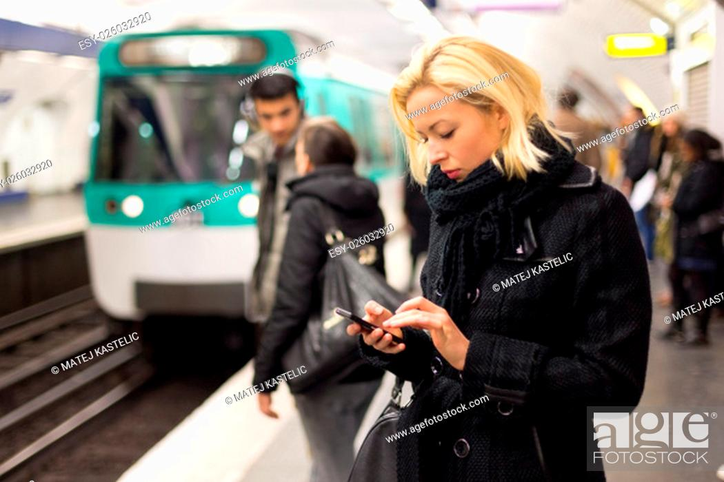 Stock Photo: Young woman in winter coat with a cell phone in her hand waiting on the platform of a railway station for train to arrive. Public transport.