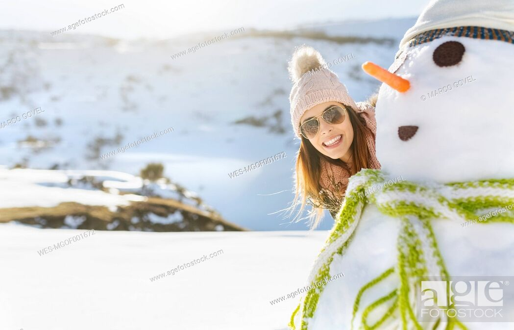 Stock Photo: Spain, Asturias, happy young woman with a snowman.