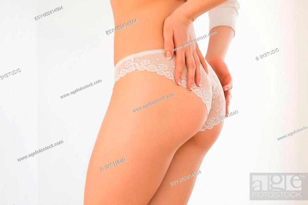 Stock Photo: Beautiful sexy lady in elegant white panties and bra. Portrait of fashion model girl indoors. Beauty blonde woman with attractive buttocks in lace lingerie.