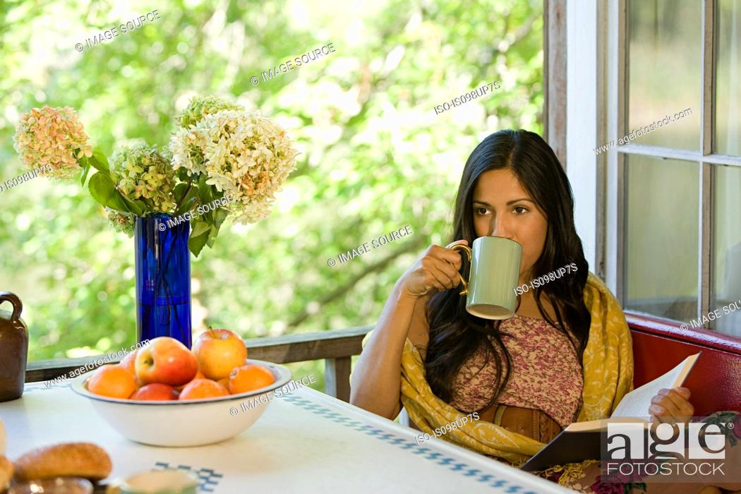 Stock Photo: Woman relaxing with a drink and a book.