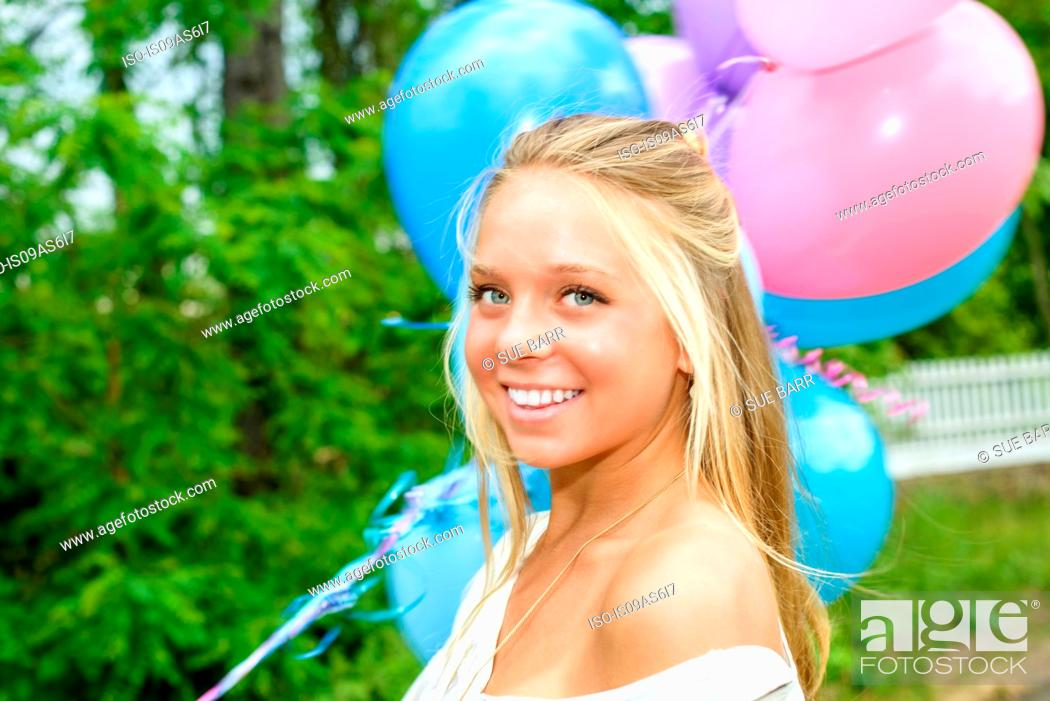 Imagen: Portrait of pretty young woman with long blond hair holding bunch of balloons.