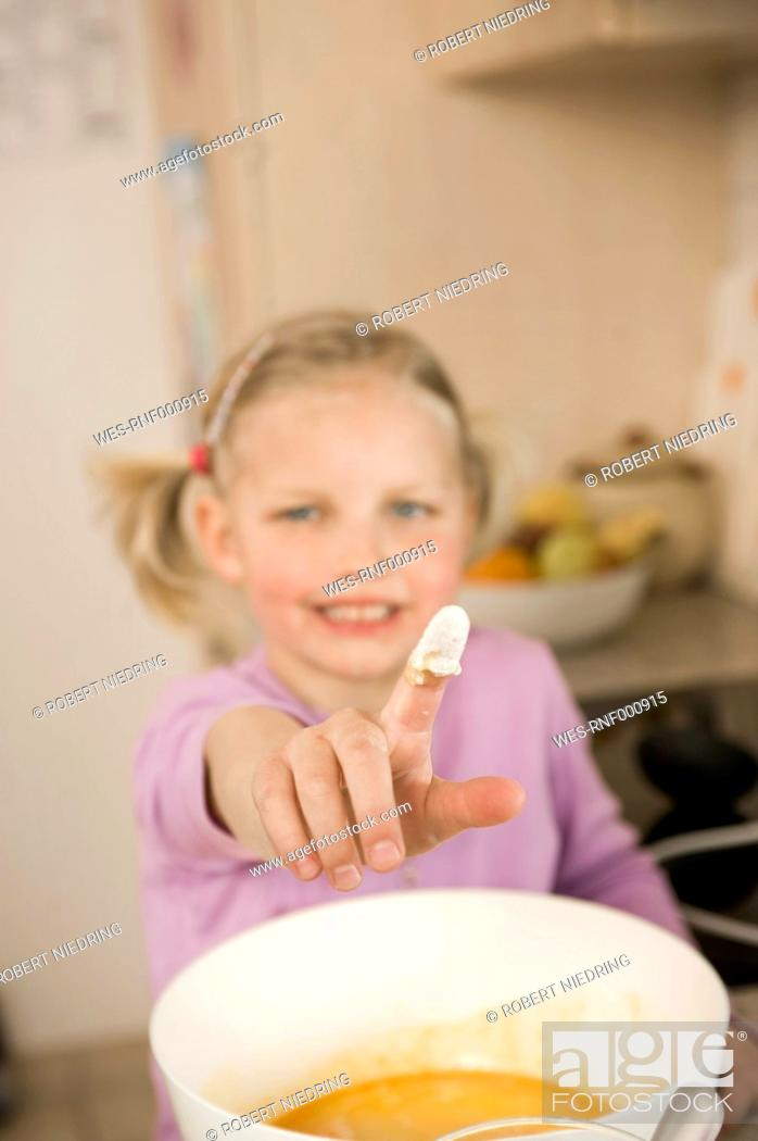 Stock Photo: Girl showing finger covered with flour, smiling, portrait.
