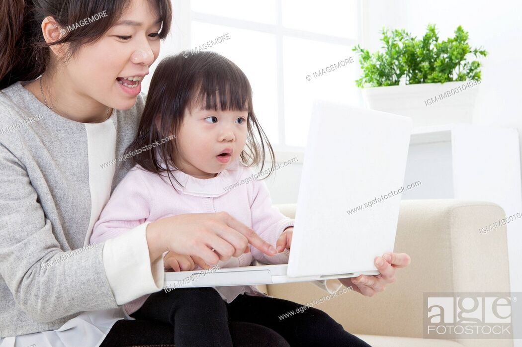 Imagen: Mother and baby girl playing laptop together,.