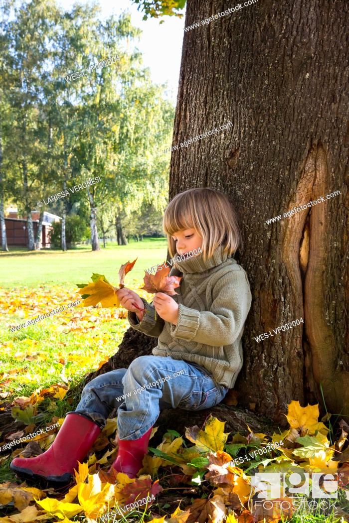 Stock Photo: Little girl leaning at tree trunk looking at bunch of autumn leaves in her hands.