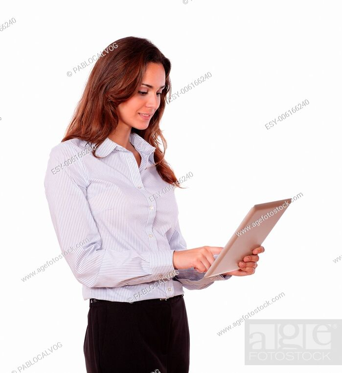 Stock Photo: Portrait of a charming young woman working on tablet pc while standing on isolated background.