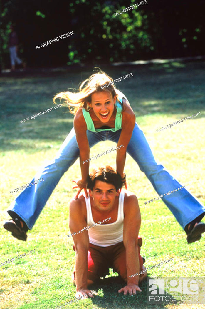Stock Photo: Portrait of Young woman hurdling over young man.
