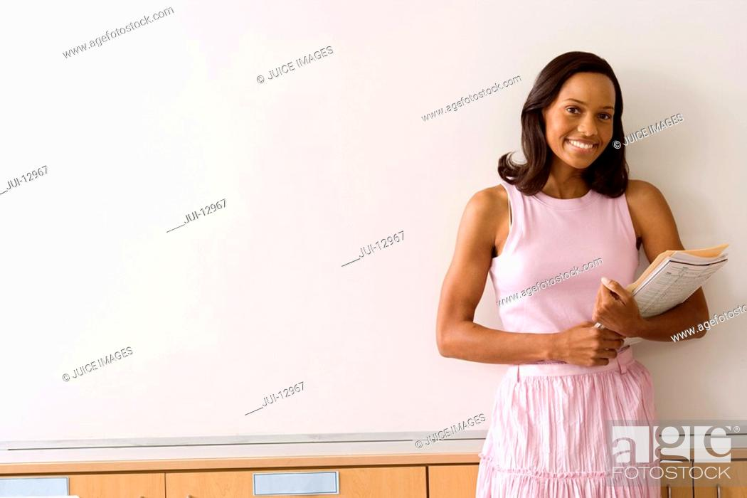 Stock Photo: Woman with paperwork by whiteboard, smiling, portrait.