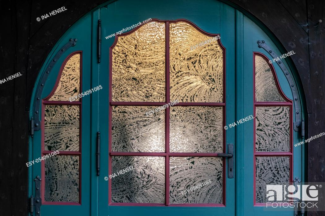 Stock Photo: vintage blue door decorated with round etched windowpanes.