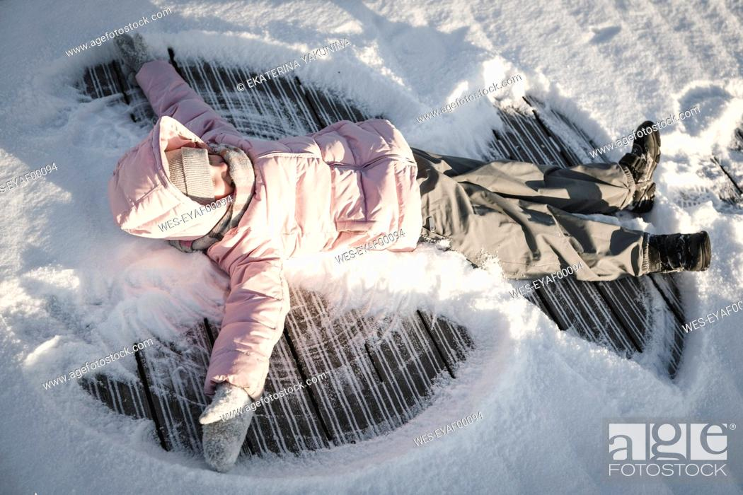 Imagen: Little girl making a snow angel.