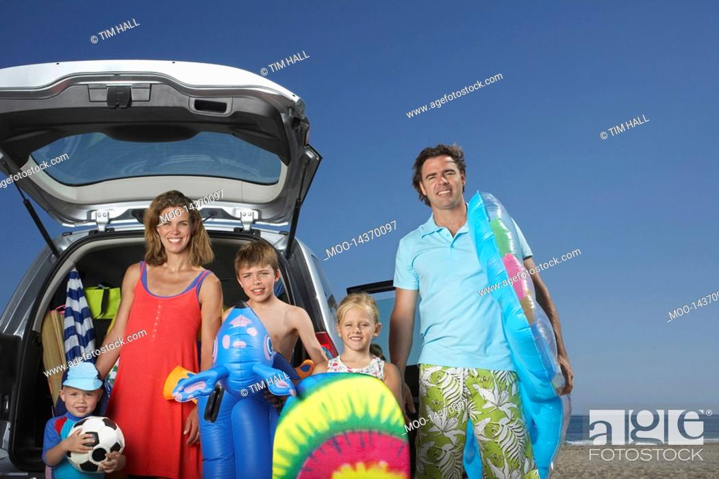 Stock Photo: Portrait of family with three children 3-11 at beach by car.