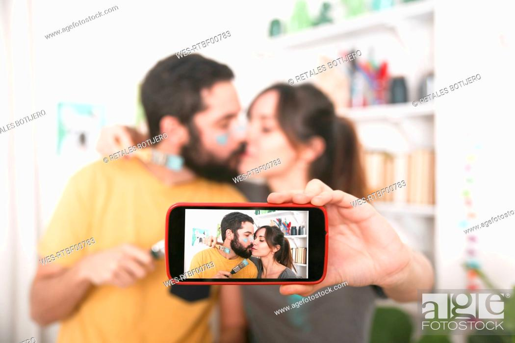 Stock Photo: Young couple kissing and taking a selfie with paintbrushes.