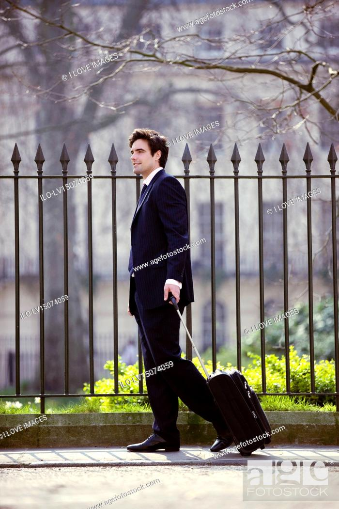Stock Photo: A businessman pulling his suitcase.