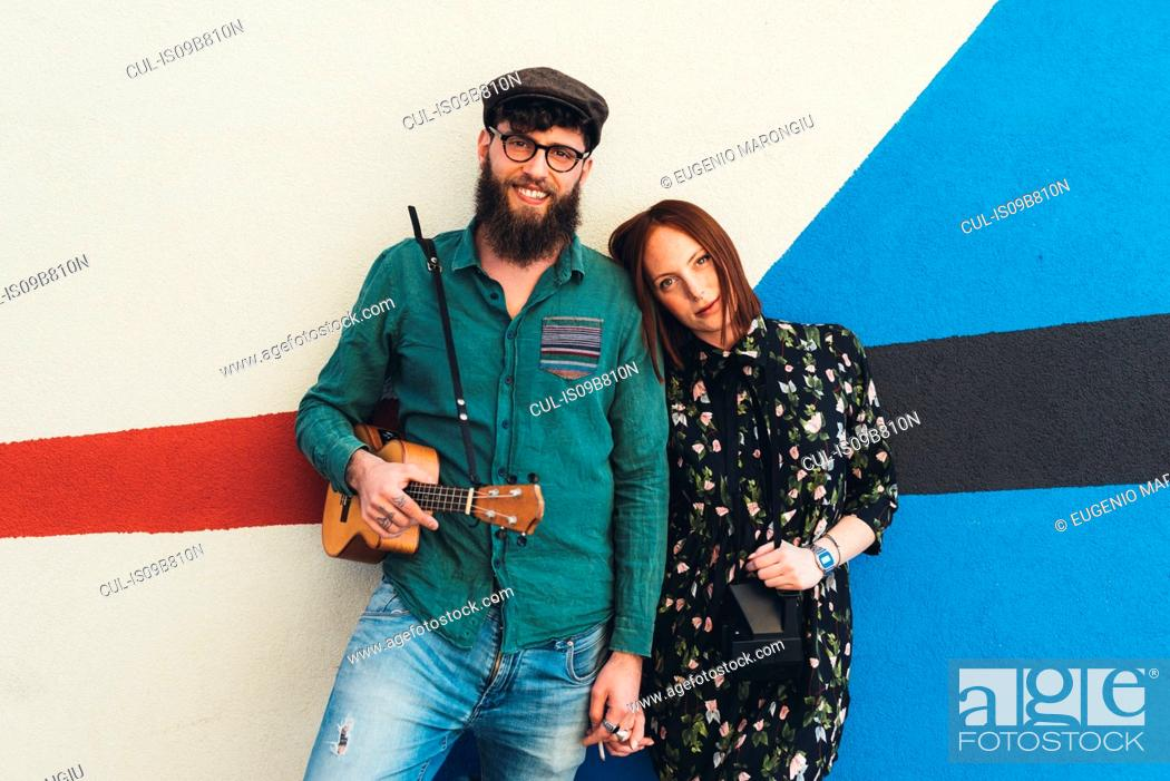 Photo de stock: Portrait of cool couple leaning against abstract wall.