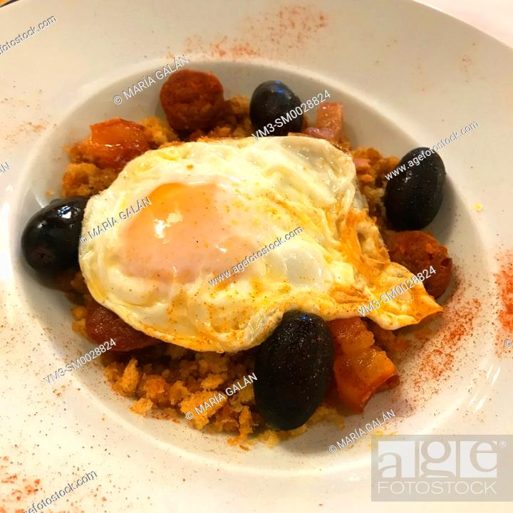 Stock Photo: Migas with fried egg, grapes and bacon. Soria, Spain.