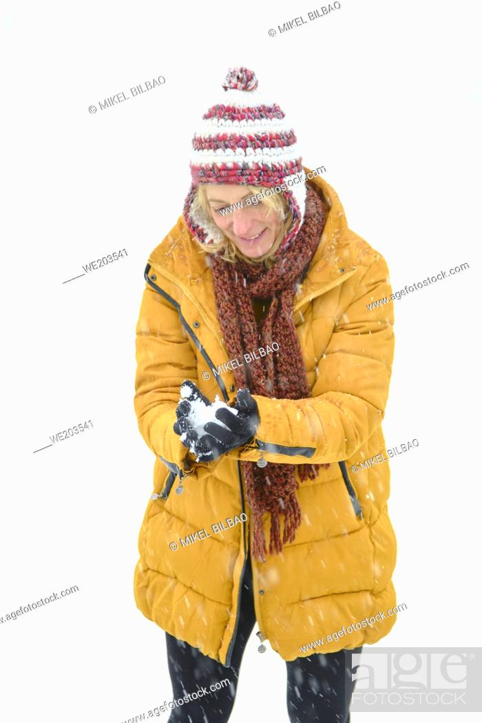 Stock Photo: Caucasian young woman making a snowball outdoor in winter time. Navarre, Spain, Europe.