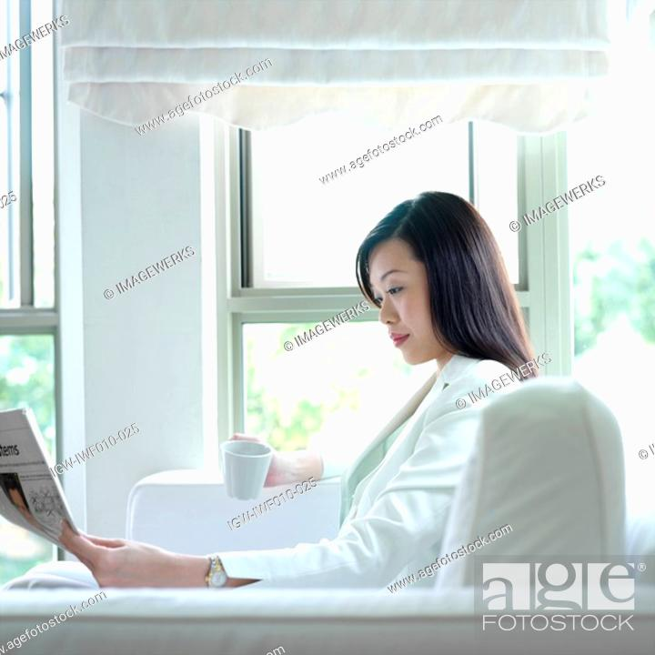 Stock Photo: Side profile of a businesswoman reading a newspaper.