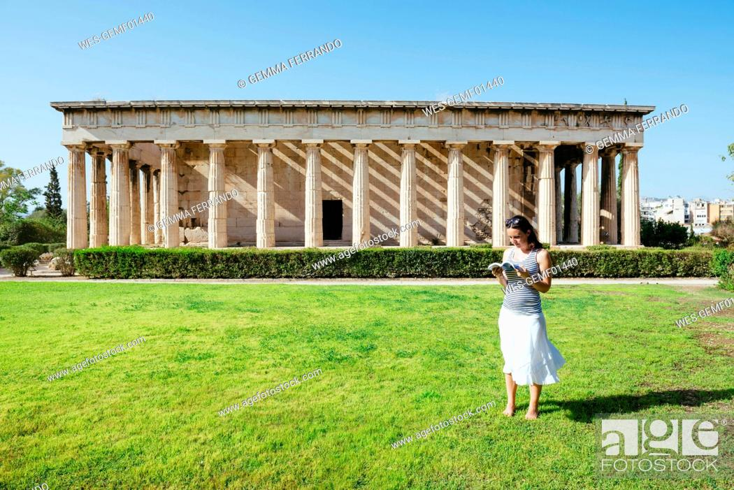 Imagen: Greece, Athens, woman reading a book in front of The Hephaisteion in the Agora.