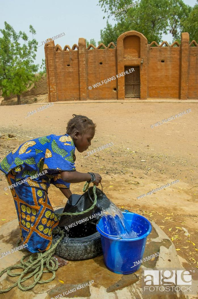 Stock Photo: A teenage girl is getting water from a well (the palace of the Bambara Kingdom in the background) in the Segoukoro village (Bambara tribe) near Segou city in.