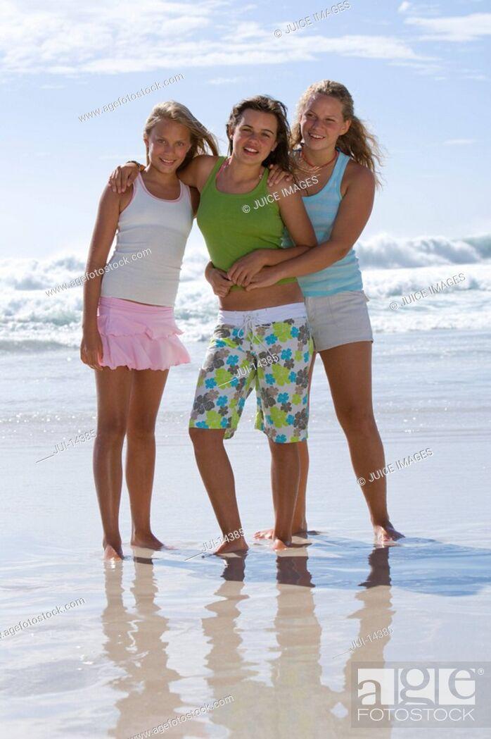 Stock Photo: Three teenage girls 14-16 arm in arm on beach, smiling, portrait.