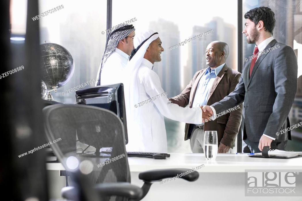 Stock Photo: Western businessmen having meeting in Middle Eastern office.