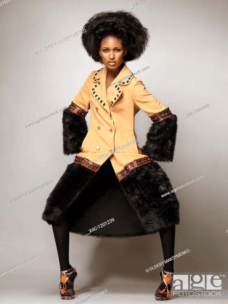 Stock Photo: High fashion photo of a young woman wearing a coat with black fur.