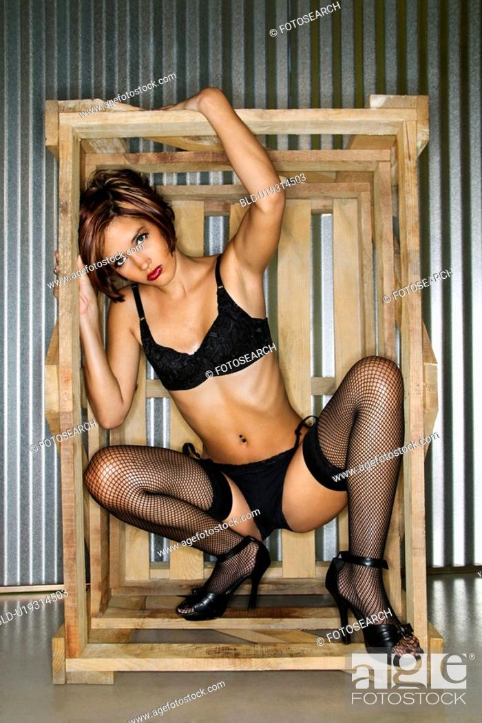 Stock Photo: Portrait of young Caucasian woman dressed in lingerie inside crate box.