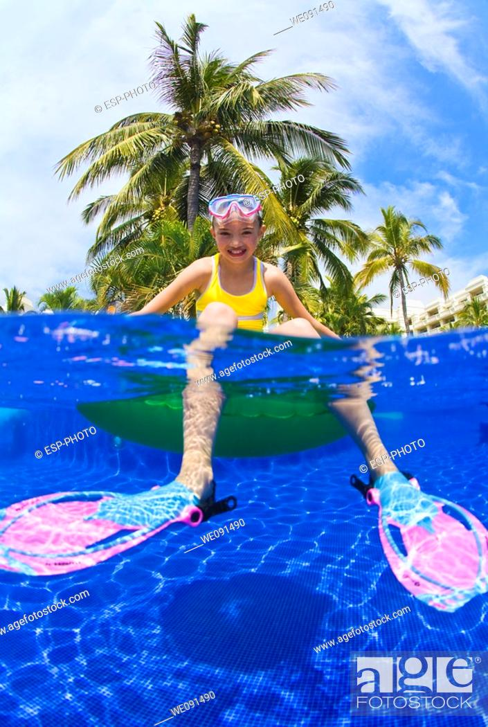 Stock Photo: Young girl sitting on float in swimming pool with snorkeling equipment.